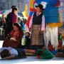 Kelzang Darchen prayer-flag pole and prostrating pilgrims, Lhasa Tibet by Jan Reurink